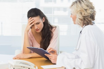 Female doctor discussing reports with patient at desk in medical office